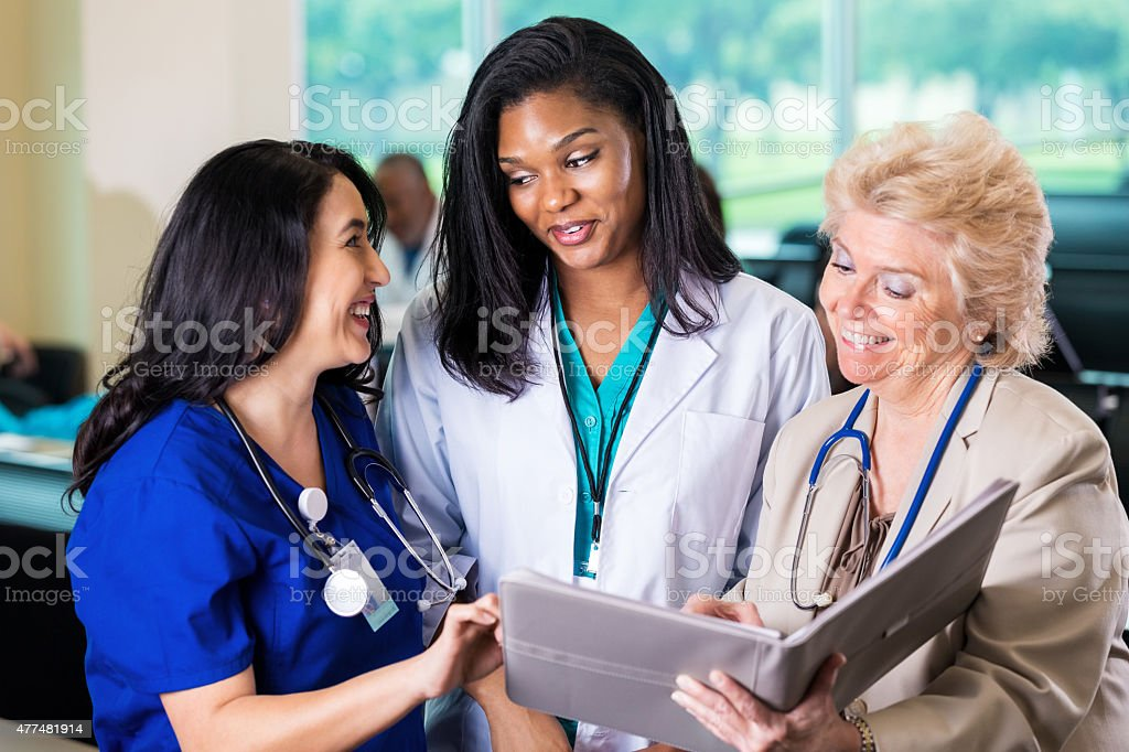 Female doctors and nurses reviewing hospital policy at healthcare conference stock photo