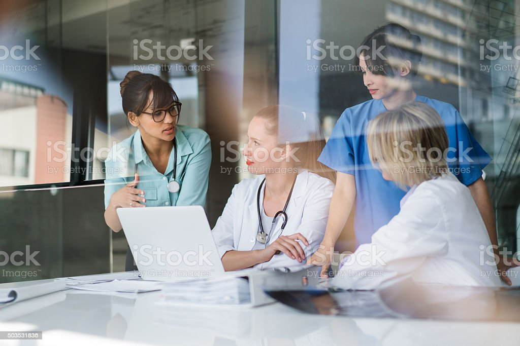 Female doctors discussing at laptop desk stock photo