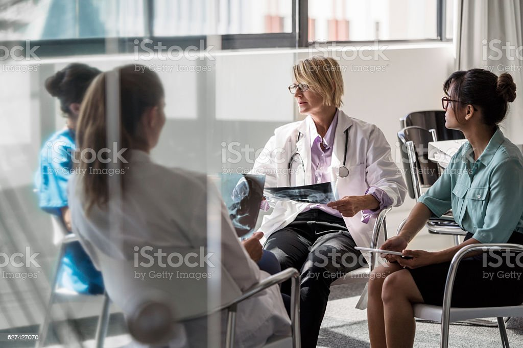 Female doctors discussing over X-ray in clinic stock photo