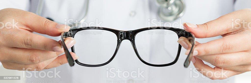 Female doctor's hand holding black glasses stock photo
