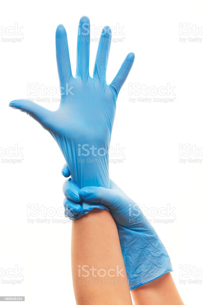 Female doctor's hands putting on blue sterilized surgical gloves stock photo