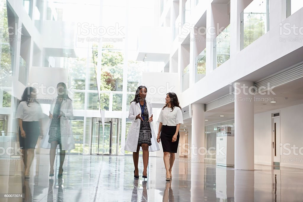 Female Doctors Talking As They Walk Through Hospital stock photo