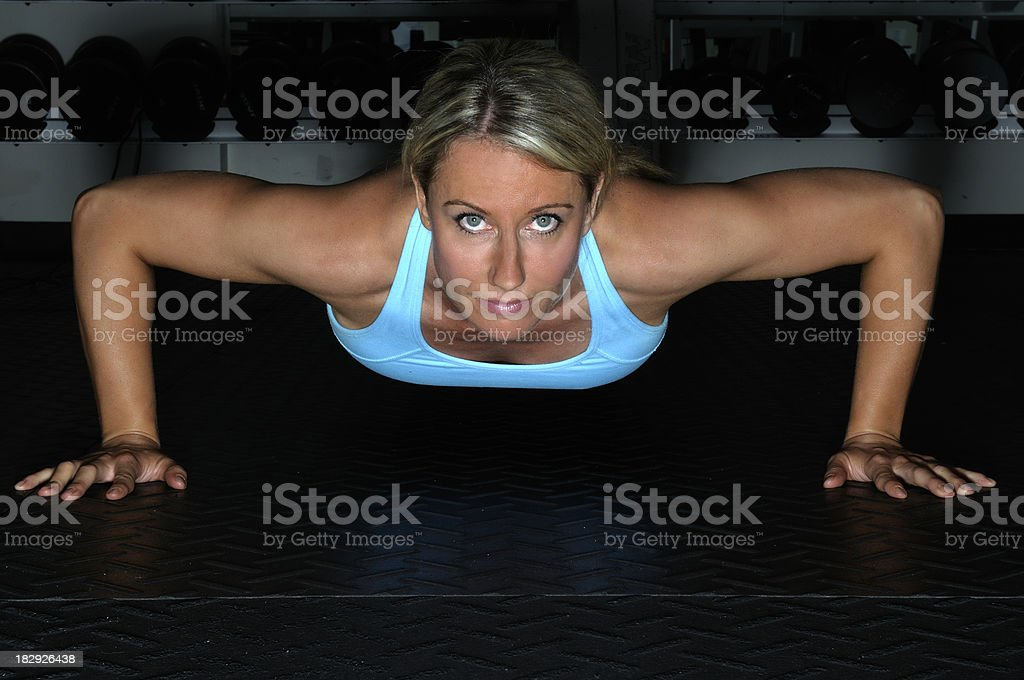 Female doing a push up isolated on black royalty-free stock photo