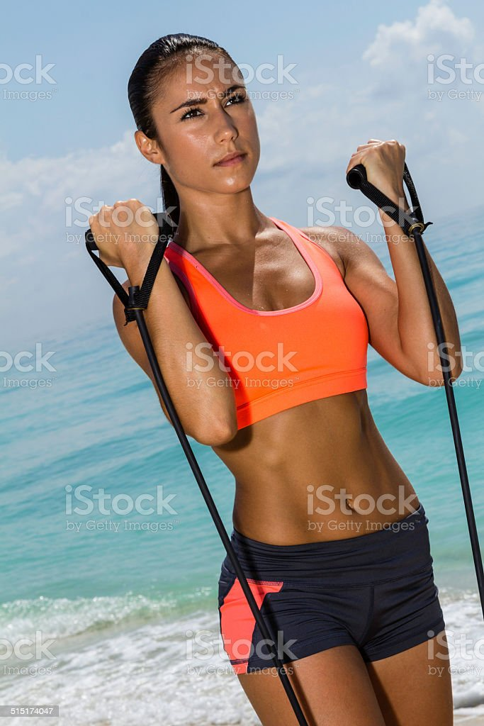 Female doing bicep curl with bands stock photo
