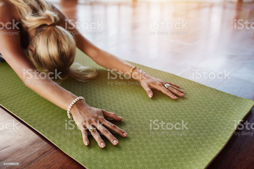 Female doing stretching workout on exercise mat stock photo