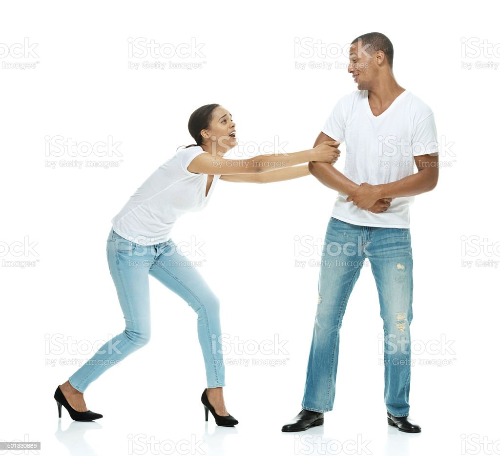 Female dragging a reluctant man stock photo