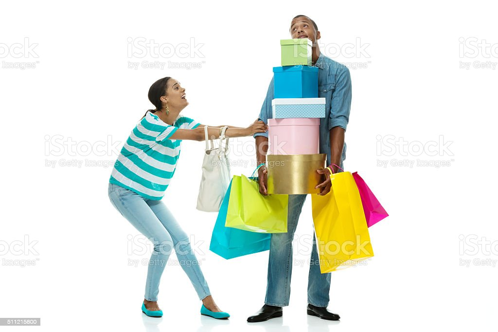 Female dragging male to do more shopping stock photo