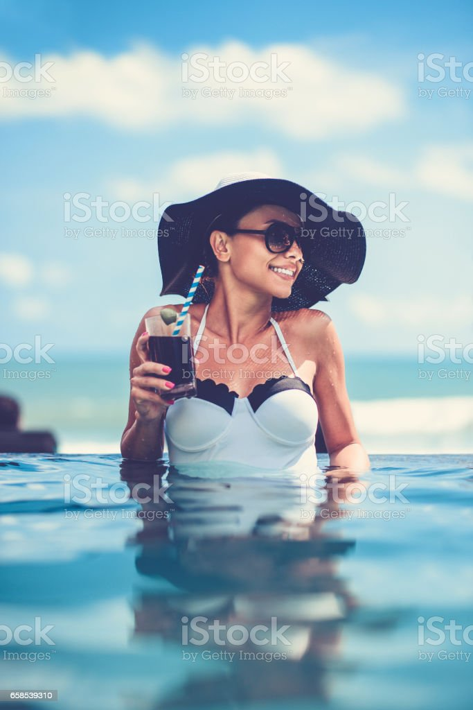 Female Drinking Cocktail and Enjoying Sunset in Infinity Swimming Pool stock photo