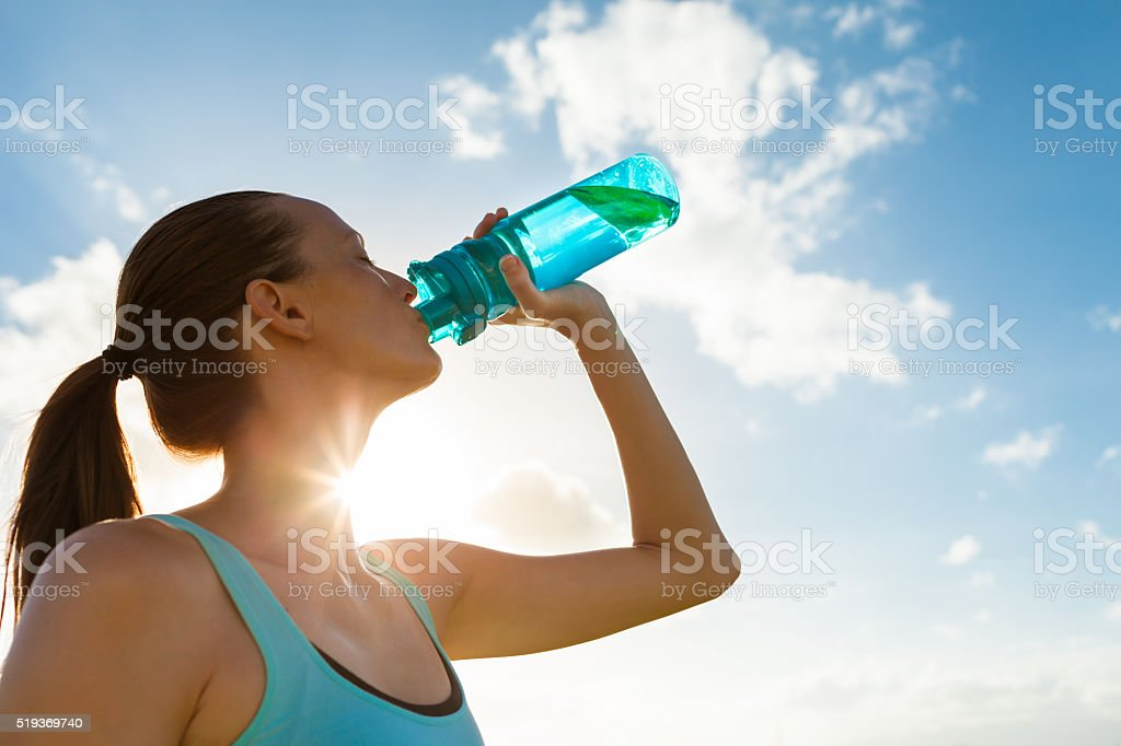 Female drinking a fresh water from bottle.