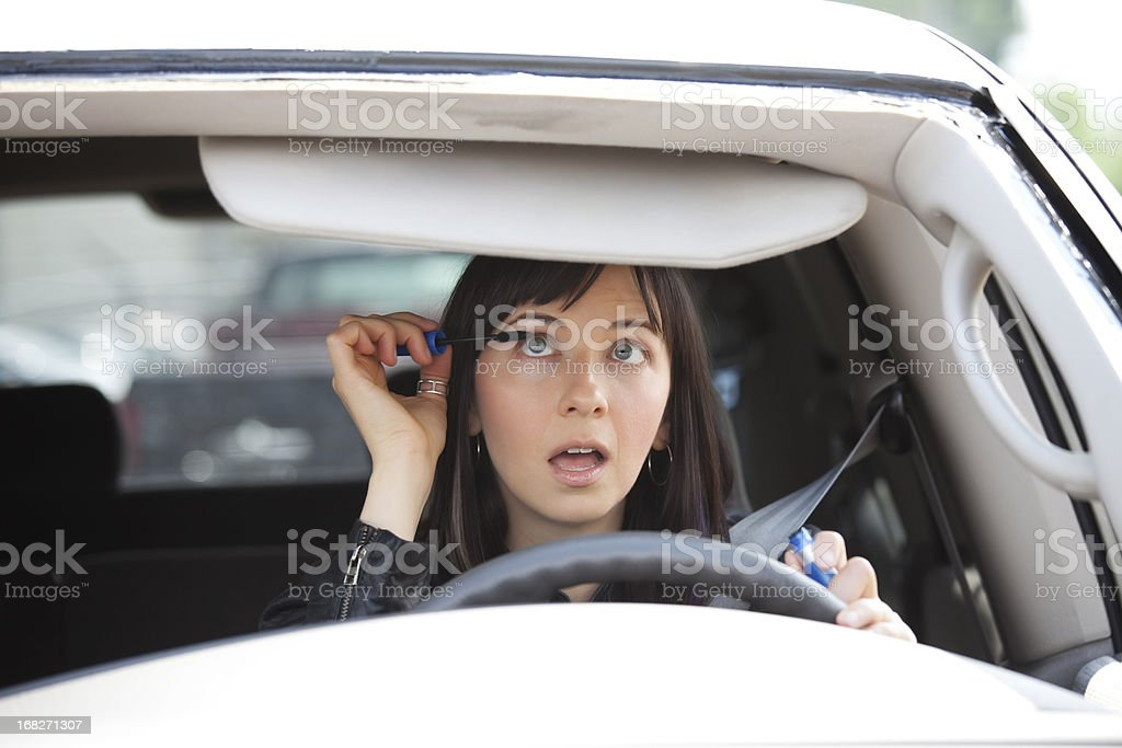 Female driver distracted while applying mascara stock photo
