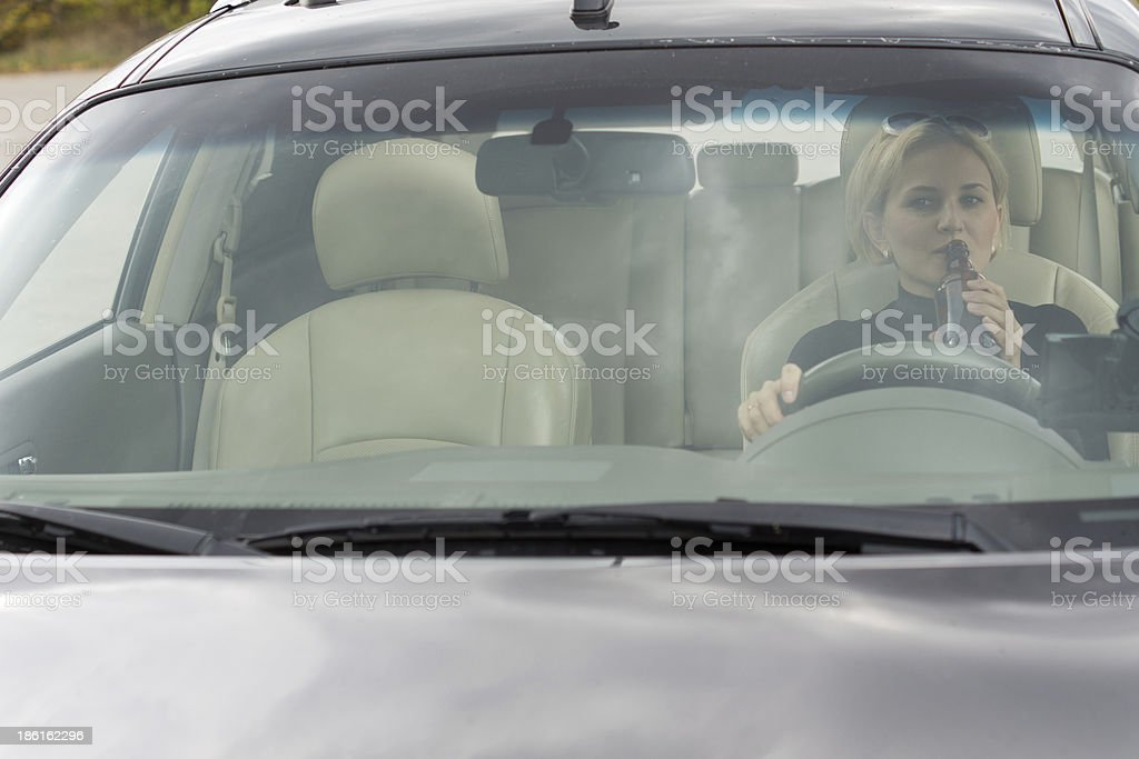 Female driver drinking alcohol in the car royalty-free stock photo
