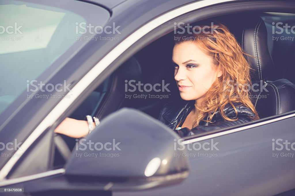 Female driver, driving a new black car. stock photo