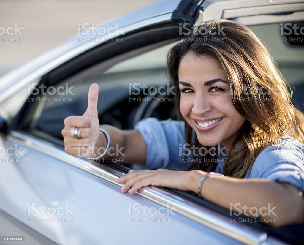 Female driver with thumbs up stock photo