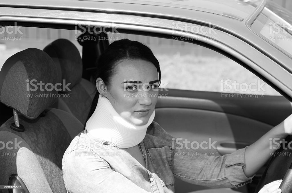 female driving with whiplash and neckbrace stock photo