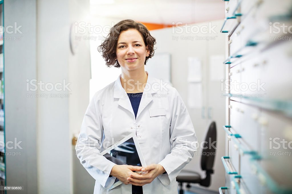 Female druggist standing with a digital tablet stock photo