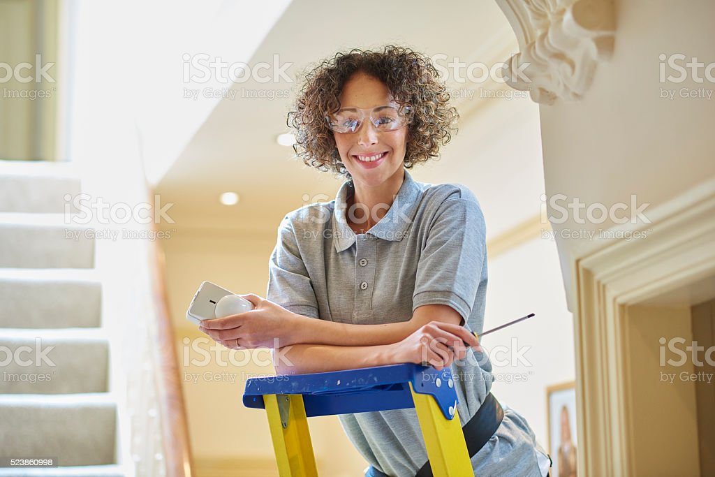 female electrician fitting alarm sensor stock photo