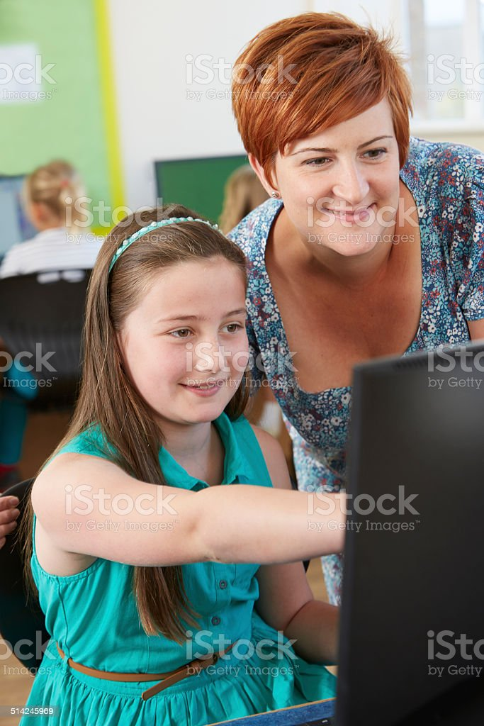 Female Elementary Pupil In Computer Class With Teacher stock photo