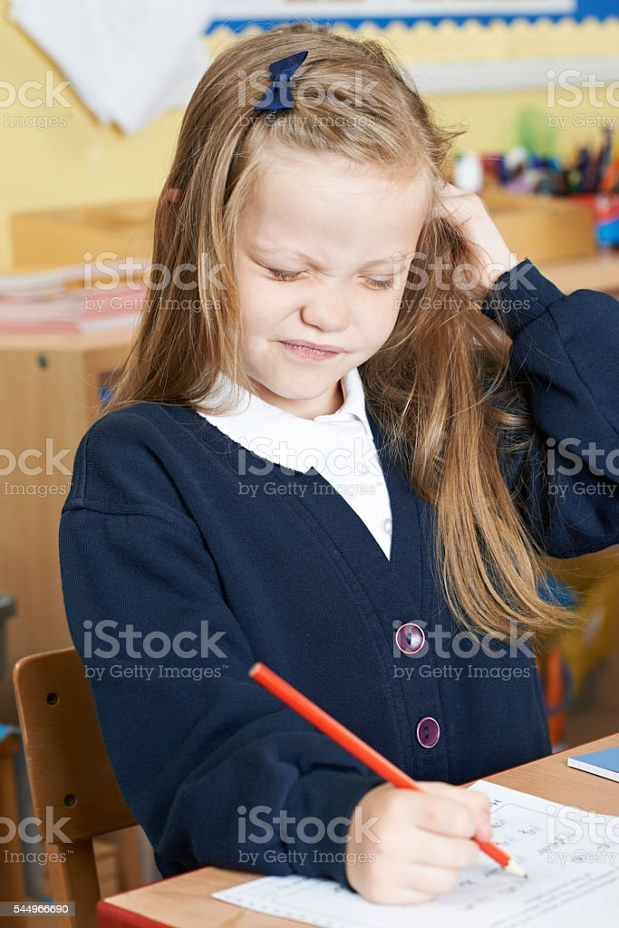 Female Elementary Pupil Suffering From Head Lice In Classroom stock photo