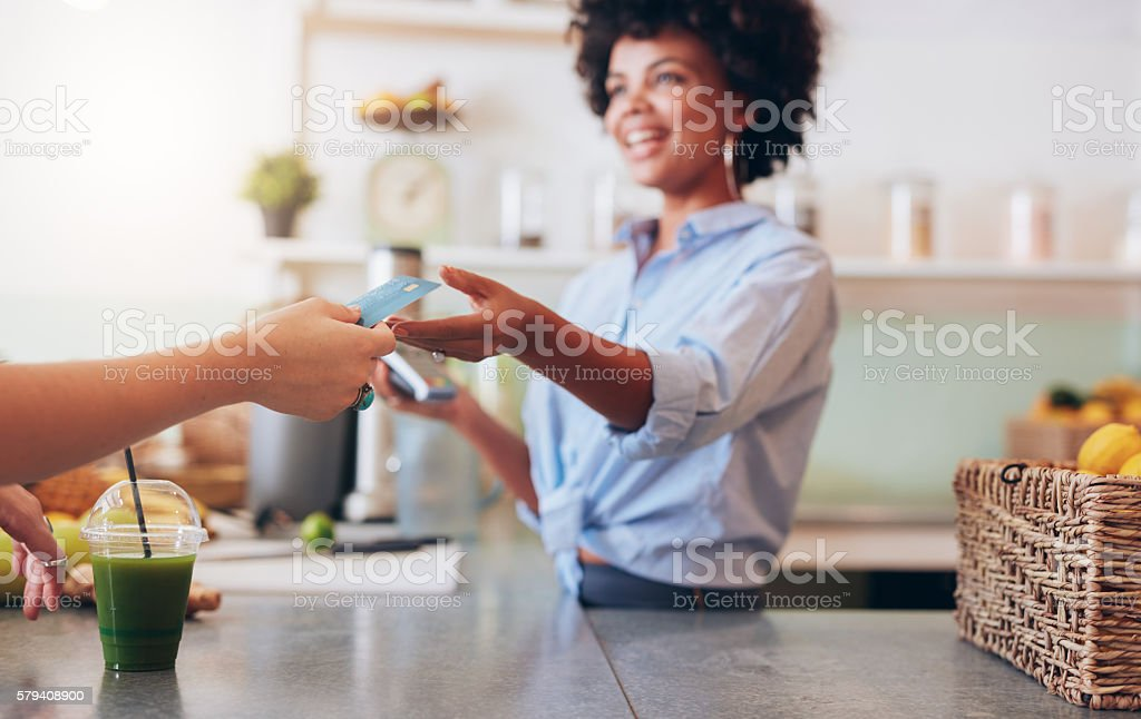 Female employee taking payment from customer stock photo