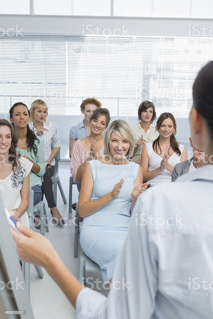 Female employees applauding their colleagues presentation stock photo