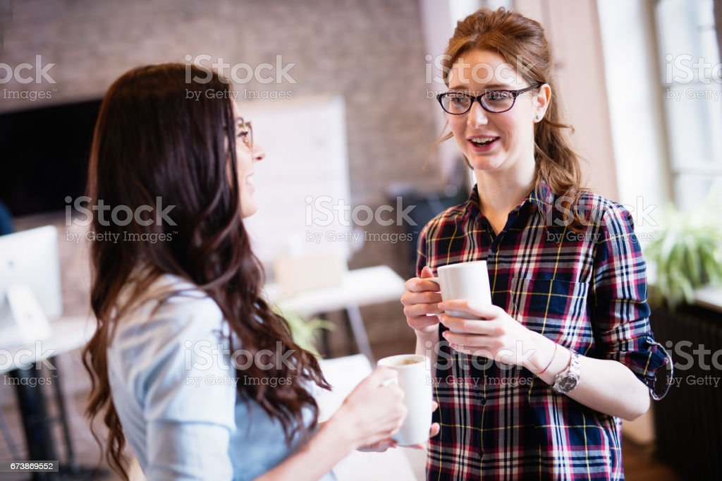 Female employees having coffee break in modern office