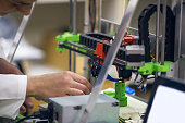 Female engineer repairing a 3D printer