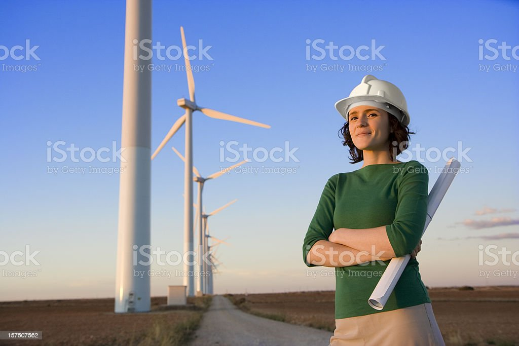 Female engineer stands in front of windmills royalty-free stock photo