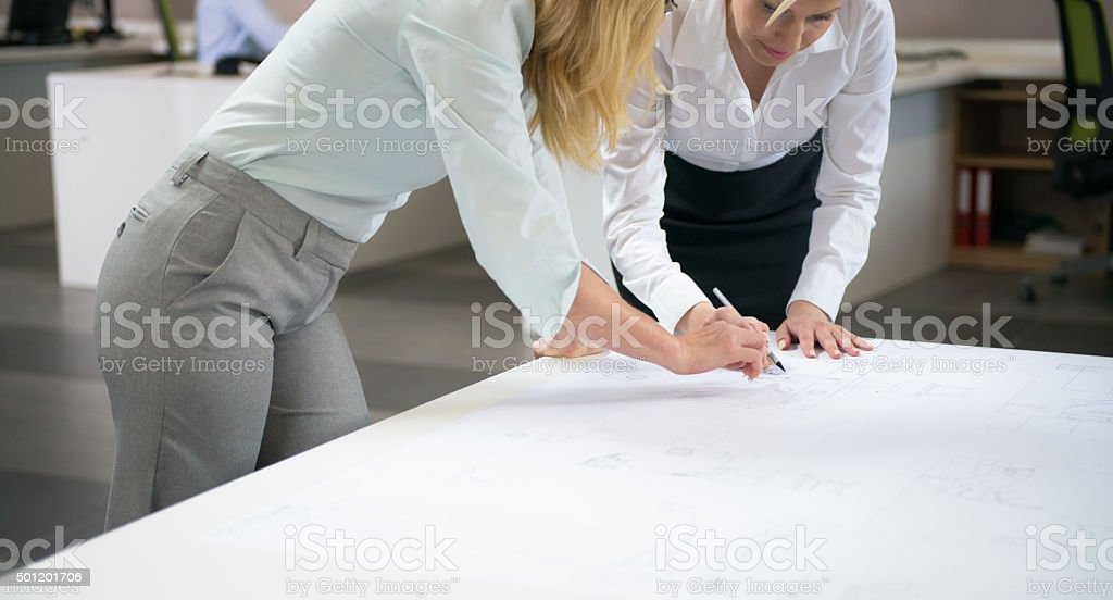 Female Engineers Reviewing Blueprints Together stock photo