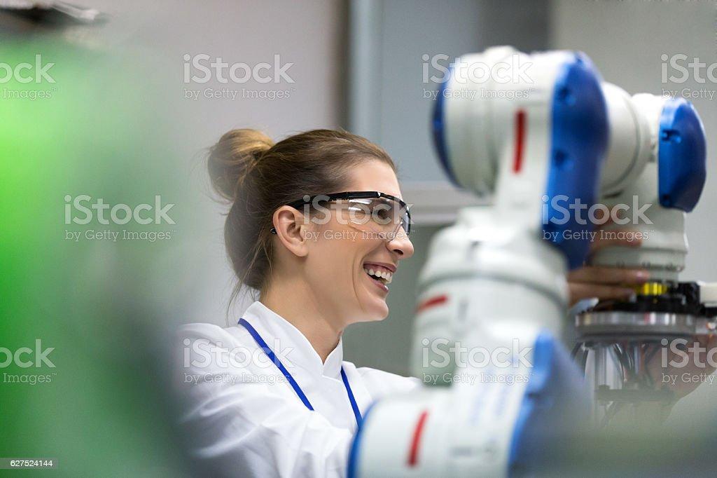 Female engineers working on robotic arm development stock photo