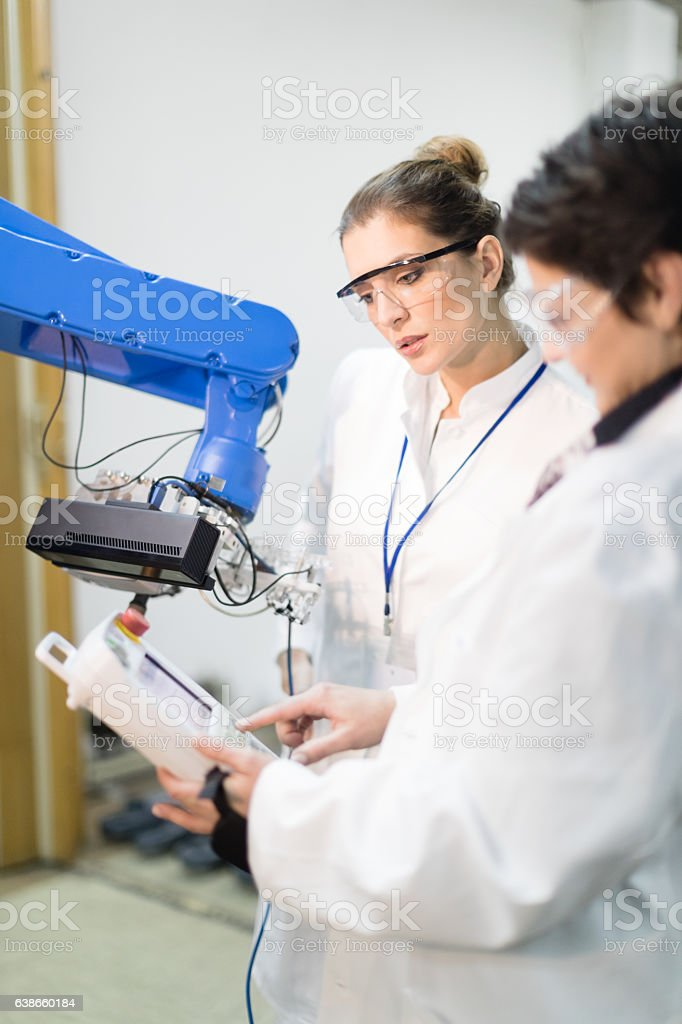 Female engineers working with robotic arm stock photo
