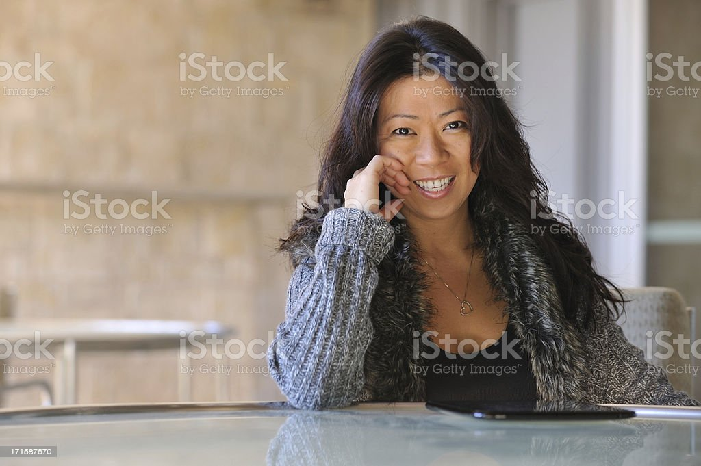 Female entrepreneur with a tablet sitting at table smiling royalty-free stock photo
