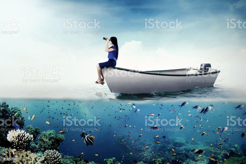 Female entrepreneur with binoculars on boat stock photo