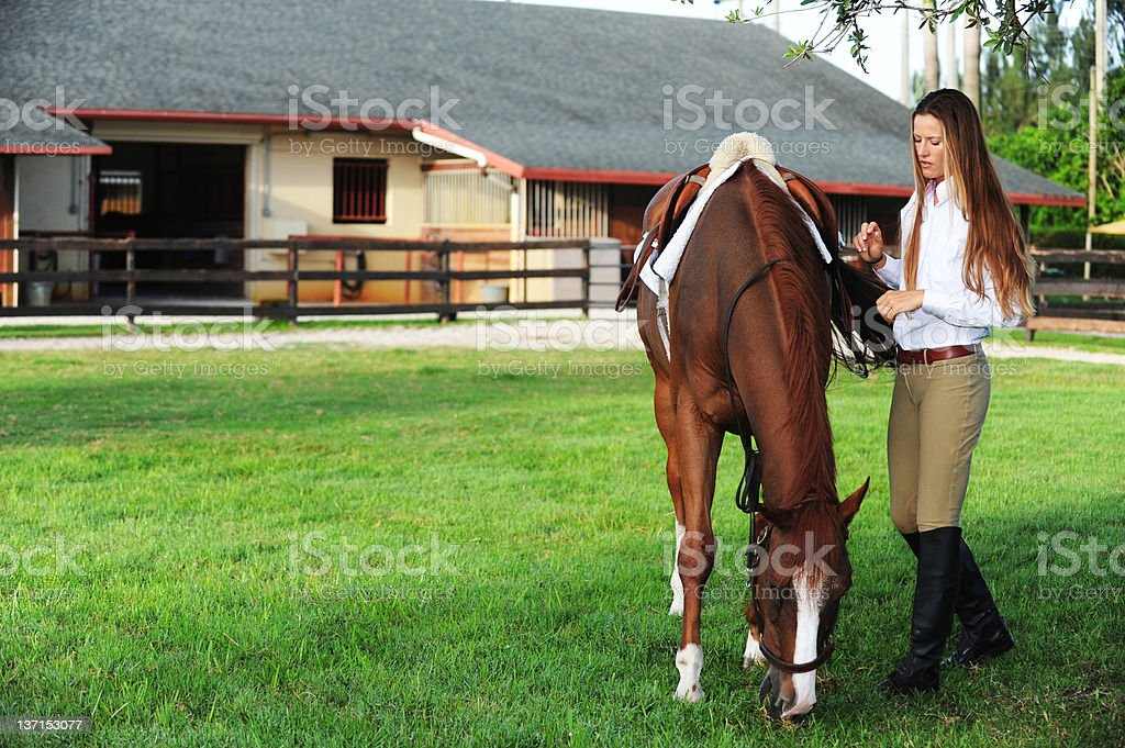 Female equestrian with chestnut horse on ranch stock photo