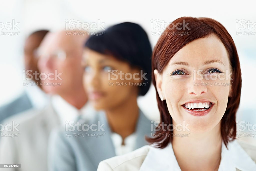 Female executive smiling with colleagues standing in row royalty-free stock photo