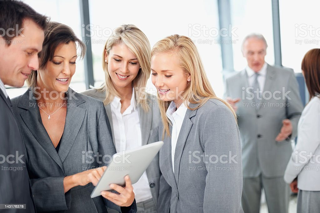 Female executive using tablet pc with colleagues royalty-free stock photo