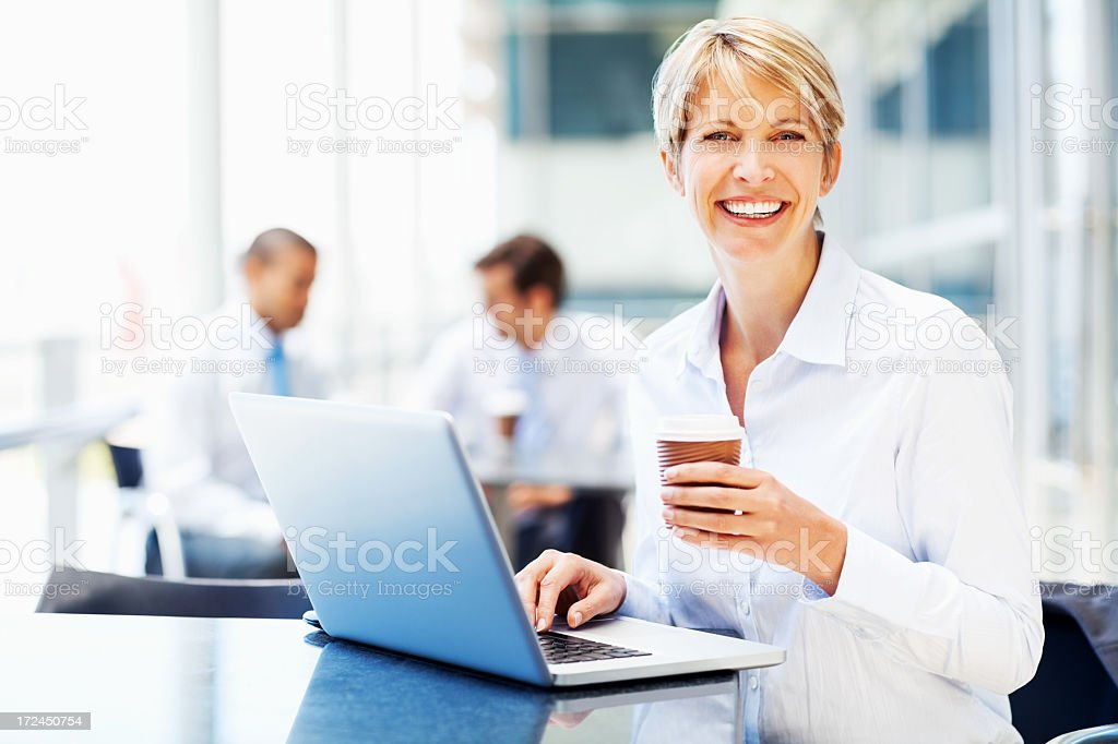 Female Executive With Laptop Holding Disposable Cup royalty-free stock photo