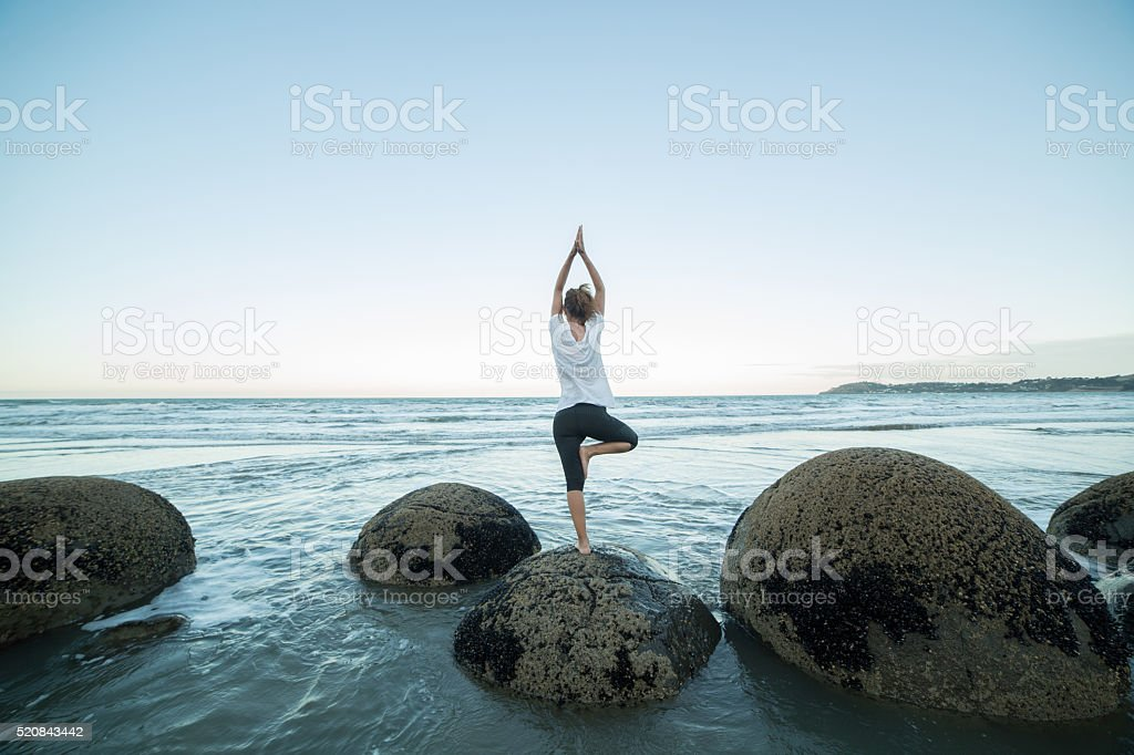 Female exercises yoga on a boulder by the sea stock photo