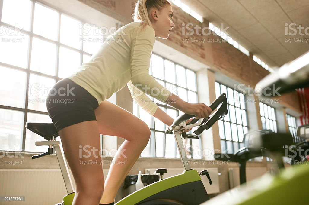Female exercising on a bike in gym stock photo