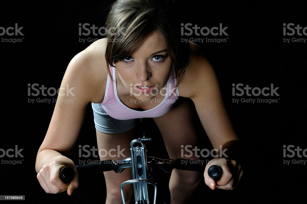 Female exercising on a bike stock photo