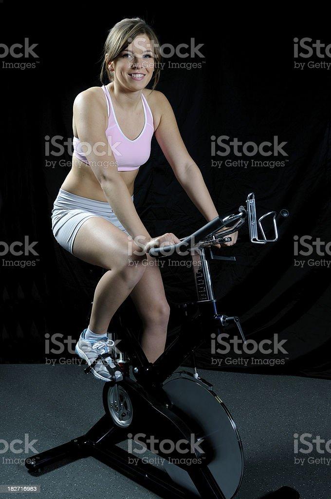 Female exercising on a bike royalty-free stock photo