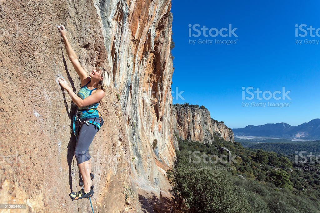 Female extreme Climber hanging on high vertical Rock stock photo
