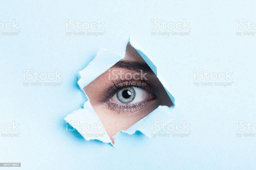 Female eye with mascara looking thru torn cardboard stock photo