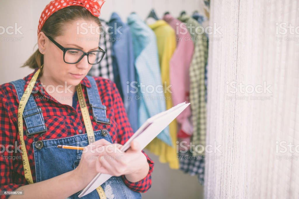 Female fashion designer hands holding drawing pad and pen making sketch of new dress. stock photo