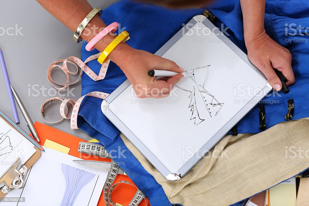 Female fashion designer hands holding drawing pad and pen making stock photo