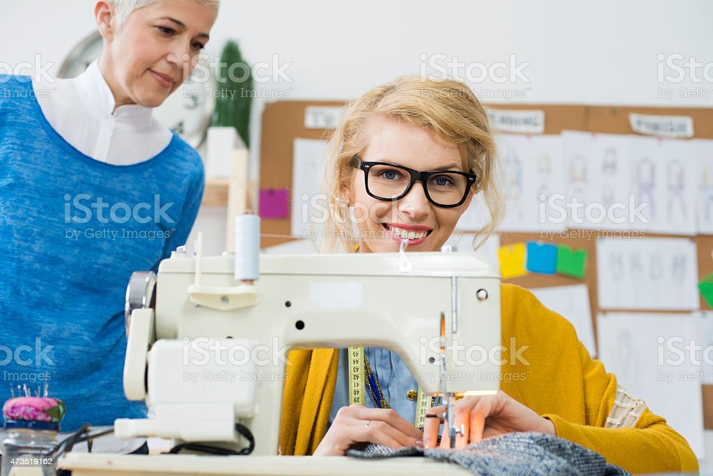 Female fashion designer using sewing machine stock photo
