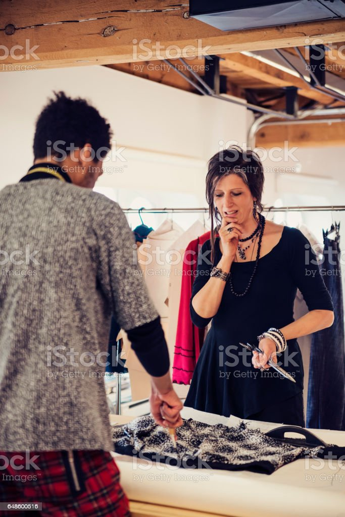Female fashion designer working with pattern maker on new creations. stock photo