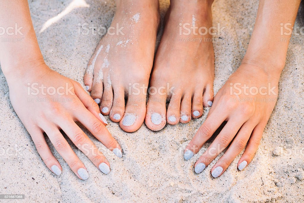Female feet and hands with manicure in summer beach sand stock photo