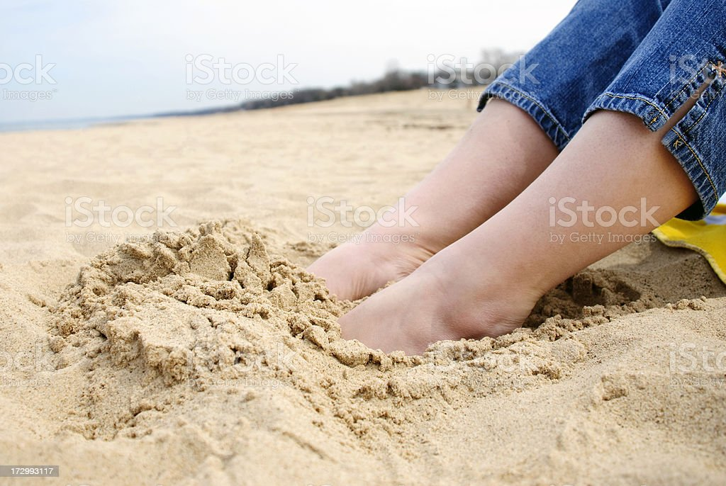Female Feet Buried in Sand at the Beach stock photo
