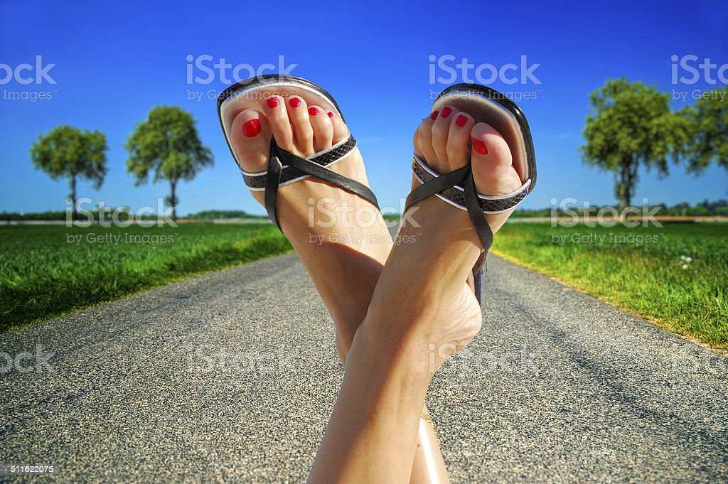 Female feet crossed with countryside in background royalty-free stock photo