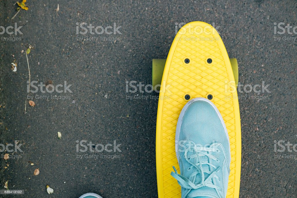 Female feet in blue sneakers on a yellow skateboard stock photo